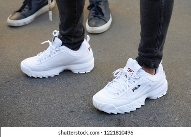 MILAN, ITALY - SEPTEMBER 23, 2018: Woman with white Fila sneakers and black trousers before Fila fashion show, Milan Fashion Week street style