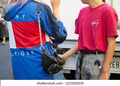 MILAN, ITALY - SEPTEMBER 23, 2018: Woman with blue, red and white Tommy Hilfiger jacket and man with pink shirt before Fila fashion show, Milan Fashion Week street style