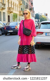 MILAN, ITALY - SEPTEMBER 23, 2018: Woman with pink velvet dress and black Balenciaga pouch before Fila fashion show, Milan Fashion Week street style