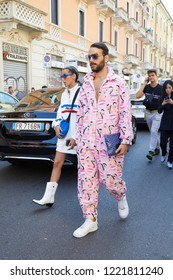 MILAN, ITALY - SEPTEMBER 23, 2018: Man with pink overalls with faces design before Fila fashion show, Milan Fashion Week street style