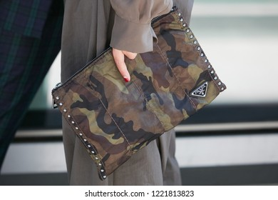 MILAN, ITALY - SEPTEMBER 23, 2018: Woman with camouflage green and brown Prada bag before Giorgio Armani fashion show, Milan Fashion Week street style