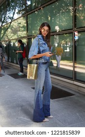 MILAN, ITALY - SEPTEMBER 23, 2018: Woman with blue denim trousers and jacket and golden leather bag before Giorgio Armani fashion show, Milan Fashion Week street style