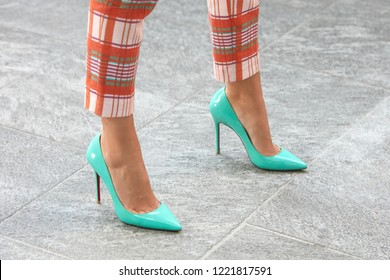 MILAN, ITALY - SEPTEMBER 23, 2018: Woman with turquoise high heel shoes and orange checkered trousers before Giorgio Armani fashion show, Milan Fashion Week street style