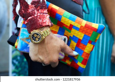 MILAN, ITALY - SEPTEMBER 23, 2018: Woman with golden Rolex Daytona chronograph, red sequin jacket and bag with colorful plastic bricks before Cristiano Burani fashion show, Milan Fashion Week style