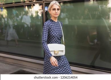 MILAN, ITALY - SEPTEMBER 23: Fashionable woman poses outside Giorgio Armani fashion show during Milan Women's Fashion Week on SEPTEMBER 23, 2018 in Milan.