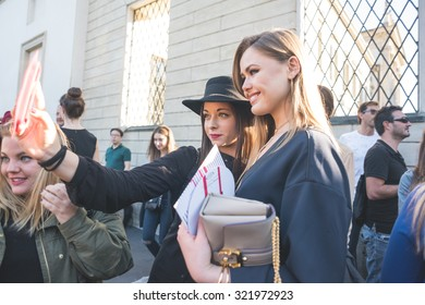 MILAN, ITALY - SEPTEMBER 25: People during Milan Fashion week, Italy on SEPTEMBER 25, 2015. Eccentric and fashionable women taking selfie waiting models and vips outside city during Milan fashion week
