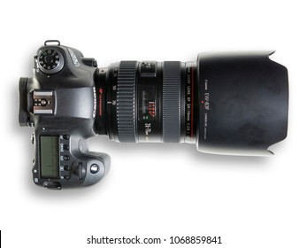 Milan, Italy - top view of a Canon EOS 6D with EF24-70mm f/2.8 L USM lens, resting on a white background. Clipping path is available