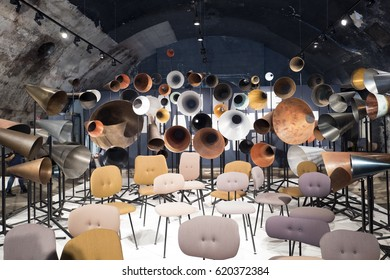 MILAN, ITALY-APRIL 06, 2017: vintage design chairs and megaphones installation on a central station's tunnel at the Fuori Salone for the international design week fair Salone del Mobile, in Milan.