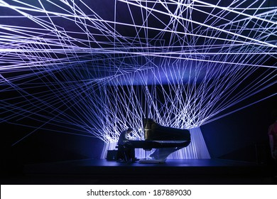 MILAN, ITALY-APRIL 08, 2014: Pianist playing music inside the lighting installation sponsored by Peugeot, at the  design Fuorisalone, during the International Fair Salone del Mobile, in Milan.