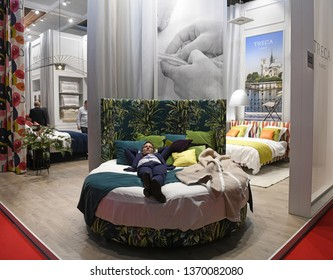 MILAN, ITALY-APRIL 09, 2019: man sleeping on a bed displayed at the international fair Salone del Mobile, in Milan.