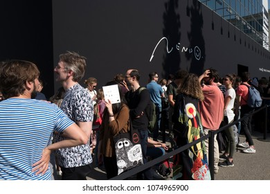 """MILAN, ITALY-APRIL 17, 2018: people queue to enter the """"Nendo: forms of movement"""" of japanese design, at the Superstudio, during the international design fair, Salone del Mobile, in Milan."""
