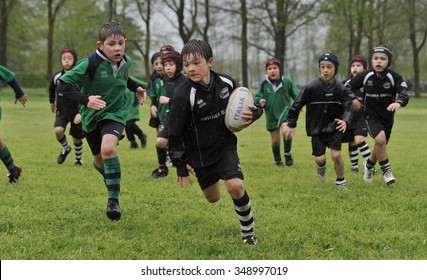 MILAN, ITALY-APRIL 21, 2014: children playing rugby during a sunday morning campus in a public park, in Milan.