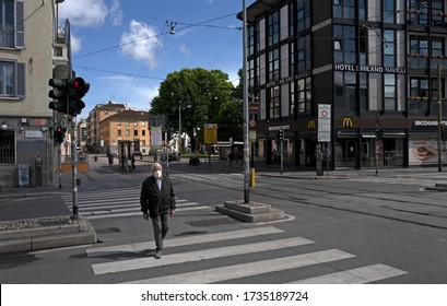 MILAN, ITALY-APRIL 29, 2020: solitary citizen wearing a protective mask walking on empty downtown streets, during the lockdown due to the coronavirus emergency, in Milan.