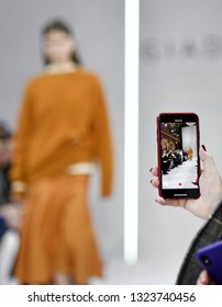 MILAN, ITALY-FEBRUARY 21, 2019: smartphone recording the female models catwalk during the Giada's fall/winter fashion show, inside the Braidense Library of the Brera's Pinacoteca, in Milan.
