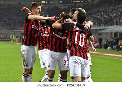 MILAN, ITALY-FEBRUARY 22, 2019: AC Milan soccer team players embrace to celebrate the win goal scored, at the san siro soccer stadium at night, in Milan.