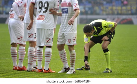 MILAN, ITALY-JANUARY 24, 2016: soccer referee spraying a barrier line on the pitch at the san siro stadium, in Milan.
