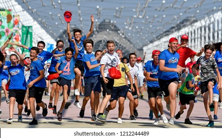 MILAN, ITALY-JULY 01, 2018: young boys and girls run and jump to celebrate at the end of a sports summer camp, in Milan.