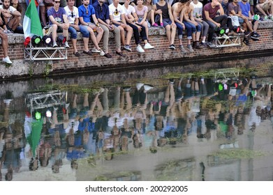 MILAN, ITALY-JUNE 20, 2014: italian soccer fans reflected on the Naviglio Grande canal, watching on a wide screen the Brazil 2014 World Cup football match Italy vs Costa Rica, in Milan.