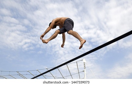 MILAN, ITALY-JUNE 29, 2019: acrobatic man walking and jumping on the elastic thread, in Milan.