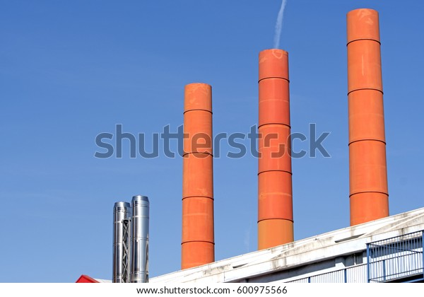 MILAN, ITALY-MARCH 02, 2017: city colorful factory with orange chimneys with blue sky in the background, in Milan.