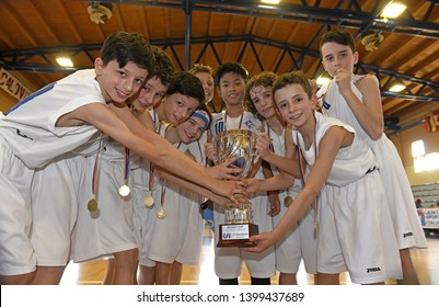 MILAN, ITALY-MARCH, 16, 2019: kids basketball team hold the trophy cup, to celebrate the win of a basketball kids final competition, in Milan.