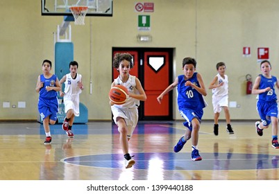 MILAN, ITALY-MARCH, 16, 2019: kids playing indoor basketball, during a final competition, in Milan.