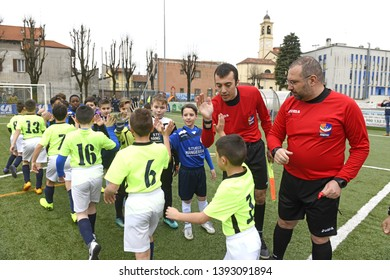 MILAN, ITALY-MARCH 17, 2019: kids soccer players greet each other by beating the five with referee, under the bell tower, in Milan.