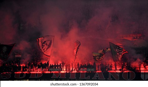 MILAN, ITALY-MARCH 17, 2019: soccer fans wave flags and red light smoke bombs, during the italian Serie A soccer match AC Milan vs Inter Milan, at the san siro stadium, in Milan.