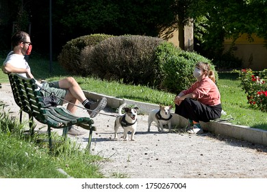 MILAN, ITALY-MAY 9, 2020: Two dogs and two people rest in the historic Guastalla Garden wearing medical mask during coronavirus epidemic period. Second phase of quarantine in Lombardy.