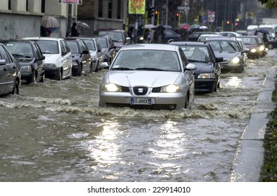 MILAN, ITALY-NOVEMBER 26, 2002: cars driving on a flooded road during a flood caused by heavy rain, in Milan.