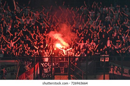MILAN, ITALY-SEPTEMBER 28, 2017: hooligans soccer fans lighting fire flares during the UEFA League match AC Milan vs Rijeka, at san siro stadium, in Milan.