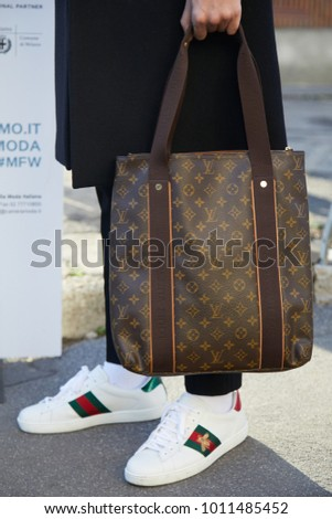 dfe3d5e74a2 MILAN - JANUARY 13  Man with Louis Vuitton bag and white Gucci shoes before  Diesel Black Gold fashion show