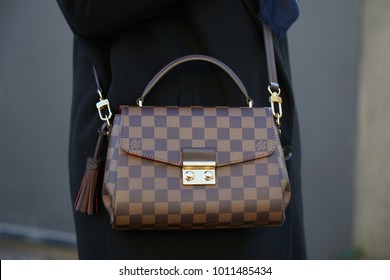 MILAN - JANUARY 13: Woman with brown checkered Louis Vuitton bag before Diesel Black Gold fashion show, Milan Fashion Week street style on January 13, 2018 in Milan.