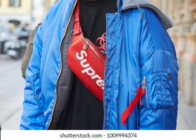 MILAN - JANUARY 14: Man with Alpha Industries blue bomber jacket and red Louis Vuitton Supreme pouch before MSGM fashion show, Milan Fashion Week street style on January 14, 2018 in Milan.