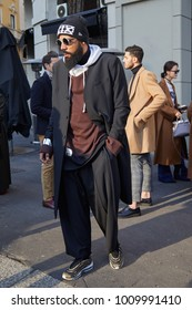 MILAN - JANUARY 14: Man with black coat and trousers before Daks fashion show, Milan Fashion Week street style on January 14, 2018 in Milan.