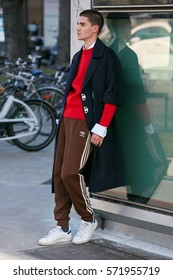 MILAN - JANUARY 14: Man with brown Adidas trousers and red sweater before Emporio Armani fashion show, Milan Fashion Week street style on January 14, 2017 in Milan.