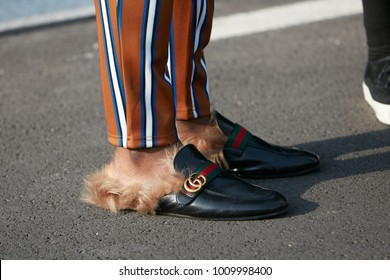 MILAN - JANUARY 14: Man with Gucci slippers with fur and striped trousers before Dsquared 2 fashion show, Milan Fashion Week street style on January 14, 2018 in Milan.
