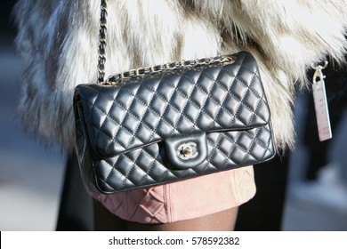 d7c81234fb40 MILAN - JANUARY 14  Woman with white fur coat and black leather Chanel bag  before