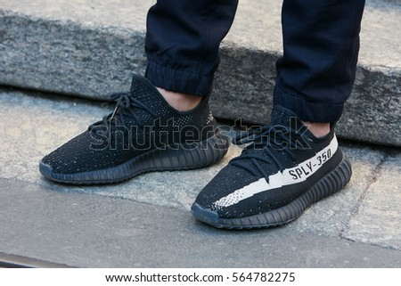 95682bff8e59f MILAN - JANUARY 15  Man with Adidas Yeezy Boost 350 black shoes before  Salvatore Ferragamo