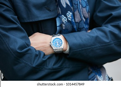 MILAN - JANUARY 15: Man with Breitling watch with blue dial and blue coat before Giorgio Armani fashion show, Milan Fashion Week street style on January 15, 2018 in Milan.