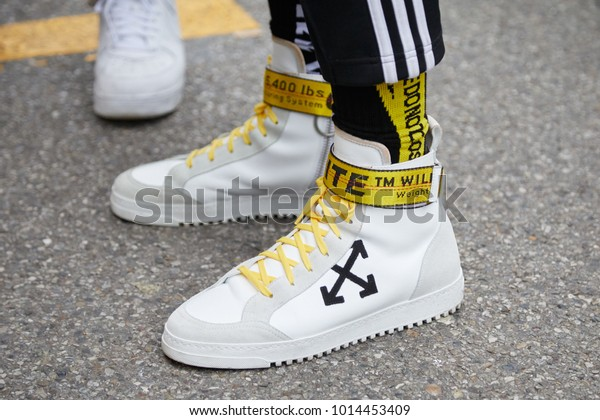 MILAN - JANUARY 15: Man with Off White sneakers with yellow belt before Represent fashion show, Milan Fashion Week street style on January 15, 2018 in Milan.