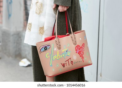 MILAN - JANUARY 15: Woman with beige leather decorated Louboutin bag before Fendi fashion show, Milan Fashion Week street style on January 15, 2018 in Milan.