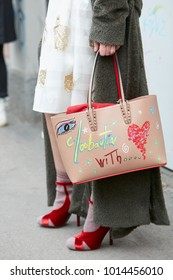 MILAN - JANUARY 15: Woman with biege decorated Louboutin leather bag with red velvet high heel shoes before Fendi fashion show, Milan Fashion Week street style on January 15, 2018 in Milan.