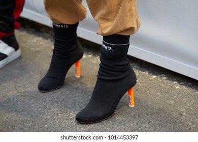 MILAN - JANUARY 15: Woman with black Vetements boots with orange heel and beige suede trousers before Represent fashion show, Milan Fashion Week street style on January 15, 2018 in Milan.