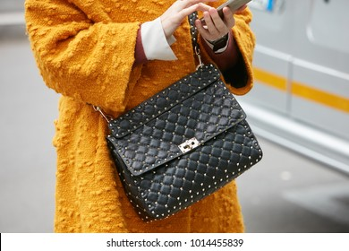 MILAN - JANUARY 15: Woman with black leather bag with golden studs and yellow coat before Giorgio Armani fashion show, Milan Fashion Week street style on January 15, 2018 in Milan.