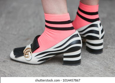 MILAN - JANUARY 15: Woman with black and white Gucci shoes and pink socks before Giorgio Armani fashion show, Milan Fashion Week street style on January 15, 2018 in Milan.