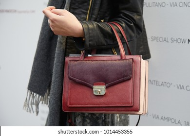 MILAN - JANUARY 15: Woman with dark red Kate Spade leather bag before Represent fashion show, Milan Fashion Week street style on January 15, 2018 in Milan.