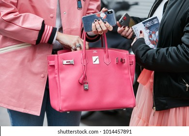 MILAN - JANUARY 15: Woman with pink Hermes leather bag before Giorgio Armani fashion show, Milan Fashion Week street style on January 15, 2018 in Milan.