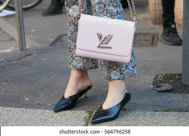 MILAN - JANUARY 15: Woman with pink Louis Vuitton leather bag and blue floral trousers before Salvatore Ferragamo fashion show, Milan Fashion Week street style on January 15, 2017 in Milan.