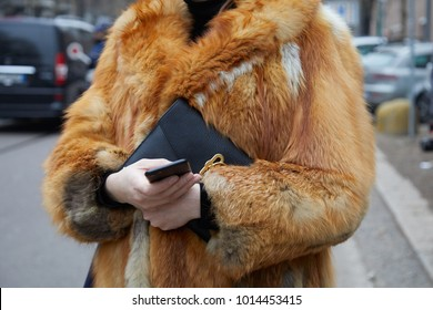 MILAN - JANUARY 15: Woman with red fox fur coat looking at smartphone before Fendi fashion show, Milan Fashion Week street style on January 15, 2018 in Milan.